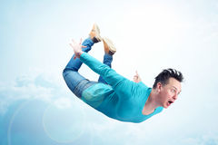 Crazy man in blue shirt and jeans is flying in the sky. Jumper concept Royalty Free Stock Photo