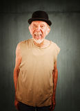 Crazy man in bowler hat. Crazy senior man in bowler hat sticking out his tongue stock photography