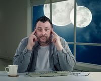 Crazy man with bulging eyes. Man with bulging eyeballs is frightened to turn around to look again at  two moons on night sky in the window. Scared middle-aged Stock Photo