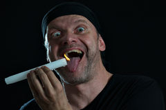 Crazy man with candle at his mouth Stock Photo