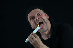 Crazy man with candle at his mouth Stock Photography