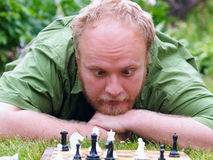 Crazy man with chess. Adult men with crazy eyes play in chess game stock images