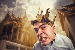 Crazy man with crown. Crazy man wearing crown on the head over asian temple royalty free stock photo