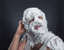 Crazy man with face completely in shaving foam. Thinks over grey Royalty Free Stock Photo