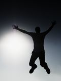 Crazy man is flying over Sun on blue sky background. Stock Photo