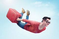 Crazy man in goggles and with red suitcase flies in the sky. Concept of vacation.  Royalty Free Stock Photos