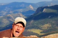 Crazy Man Hanging on the side of a Mountain Royalty Free Stock Photography