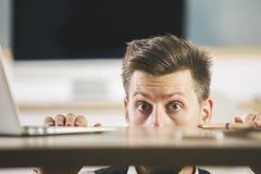 Crazy man hiding behind table Stock Photos