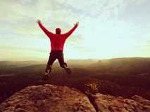 Crazy man. Hiker is jumping  on the rocky peak. Wonderful mood in rocky mountains, Royalty Free Stock Image