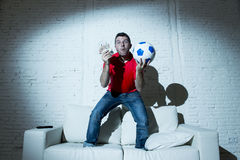 Crazy man holding money and soccer ball watching football on tv internet online bet gambling Stock Photos