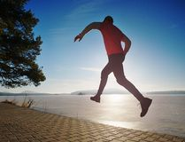 Crazy man jumping while joogging at morning spring lake. Bay. Sunny morning with clear blue sky above young workout ultra trail taking summer sportswear smart stock photo