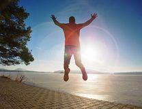Crazy man jumping while joogging at morning spring lake. Bay. Sunny morning with clear blue sky above young workout ultra trail taking summer sportswear smart stock photography