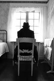 Crazy man. Male mental patient sitting in front of a window with hat and black coat, barefoot royalty free stock photography