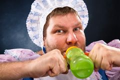 Crazy man with a pacifier. Crazy man sucking baby bottle stock photo
