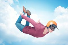 Crazy man in red helmet and goggles is flying in the sky. Concept of extreme jumping royalty free stock images