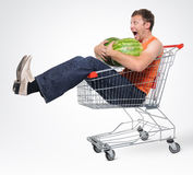 Crazy man in shopping-cart with two watermelon. On background stock photos