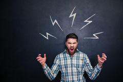 Crazy man shouting and standing under drawn lightnings over blackboard Stock Photos