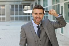 Crazy man stabbing himself in the head.  Stock Photography