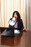 Crazy manager woman shouting in megaphone. Crazy manager woman sitting on chair at table and shouting in megaphone royalty free stock photos