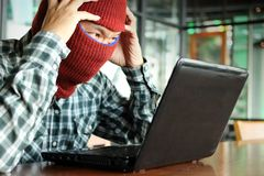 Crazy masked hacker wearing a balaclava touching on head between stealing data from laptop. Internet crime concept. Crazy masked hacker wearing a balaclava Stock Photos