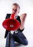 The crazy men. A crazy businessman shouting through a megaphone Royalty Free Stock Image