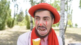 Crazy mime is vilely and disgusted at eating ice cream on the street. Crazy mime eats nasty and unpleasantly ice cream on the park stock video