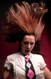 Crazy model in school uniform. Half body portrait of crazy young model shouting in school uniform with long hair blowing upwards; studio background royalty free stock image