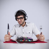 Crazy about music. Crazy young man eating music at his dinner plate Royalty Free Stock Images