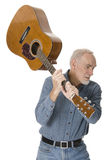 Crazy old man with guitar. Angry-looking old man wielding a guitar as if to smash it. White background Stock Images