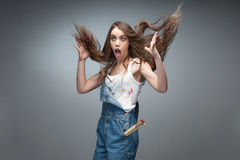 Crazy painter. Surprised painter woman screaming over gray background Stock Images