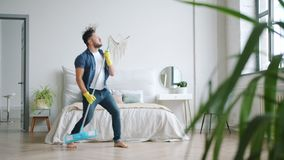Crazy person having fun at home singing in mop dancing washing floor alone. Crazy person attractive guy is having fun at home singing in mop dancing washing stock video