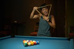 Crazy player. Female billiard player with triangle making crazy face royalty free stock images
