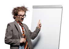 Crazy professor. / scientist / lecturer with mad hairstyle wearing horn rimmed glasses and fake mustache standing in front of a whiteboard and pointing it stock photo