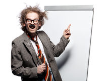 Crazy professor. / scientist / lecturer with mad hairstyle wearing horn rimmed glasses and fake mustache standing in front of a whiteboard and pointing it with royalty free stock photography