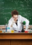 Crazy professor makes attention gesture. Mad professor makes attention gesture working in his laboratory Stock Image
