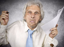 Crazy professor. Crazy old professor holding paper and pencil Royalty Free Stock Photo