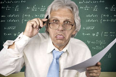 Crazy professor. Crazy old professor holding pencil and paper Stock Images