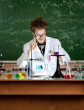 Crazy professor shows attention gesture. Mad professor shows attention gesture in his laboratory Royalty Free Stock Photo