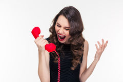 Crazy raged retro styled female shouting in red telephone receiver Stock Photography