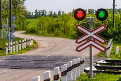 Crazy railway traffic lights with a green and red signal at the same time. Railway and road crossing stock image