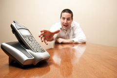 Crazy man reaching for the phone. A crazy reaches for a modern cordless phone Royalty Free Stock Images