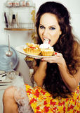Crazy real woman housewife on kitchen, eating perfoming, bizare. Girl celebrating womans day Stock Photo