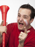 Crazy Red Team Supporter. Man in red supporters gear, holding a vuvuzela, cheering wildly Royalty Free Stock Images