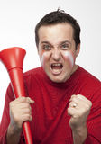 Crazy Red Team Supporter. Man in red supporters gear, holding a vuvuzela, cheering wildly Royalty Free Stock Photos
