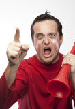 Crazy Red Team Supporter. Man in red supporters gear, holding a vuvuzela, cheering wildly and aggressively Royalty Free Stock Photography