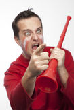 Crazy Red Team Supporter. Man in red supporters gear, holding a vuvuzela, cheering wildly and aggressively Stock Images