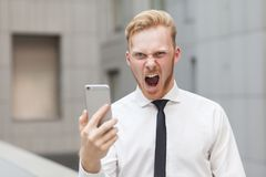 Crazy roar and looking at camera. Red head businessman. Close up, focus on face Stock Photo