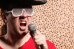 Crazy rock and roller singer with a big black hat, party glasses in front of a cheetah skin background Stock Photo