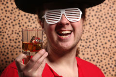 Crazy rock and rollerer with a big black hat, party glasses and a glass of whiskey in front of a cheetah skin background Royalty Free Stock Photos