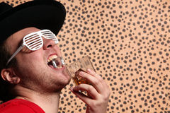 Crazy rock and rollerer with a big black hat, party glasses and a glass of whiskey in front of a cheetah skin background Royalty Free Stock Photography